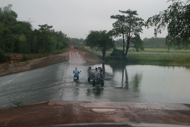 Motorbike and tractor on flooded road.