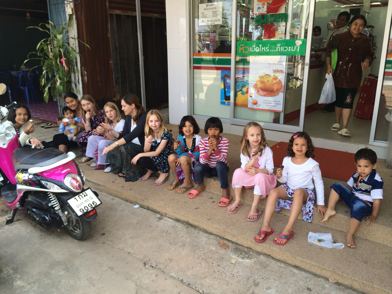 Kids eating ice cream on the steps on a 7/11